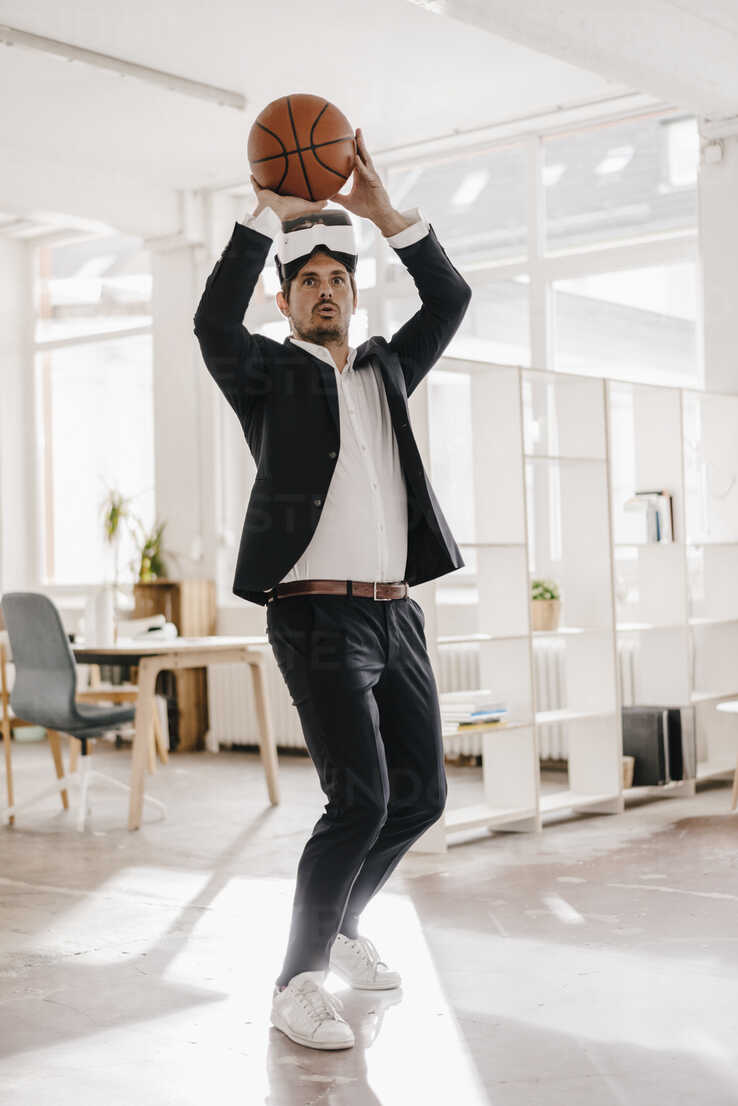 Businessman wearing VR glasses playing basketball in office - KNSF01292 - Kniel Synnatzschke/Westend61