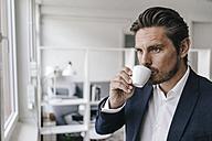 Businessman having a coffee at the window - KNSF01304