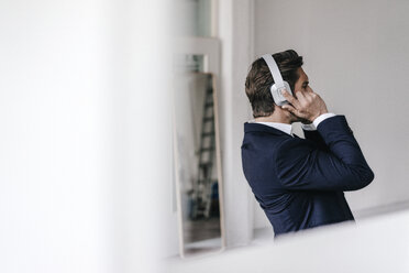 Businessman listening to music on headphones - KNSF01316