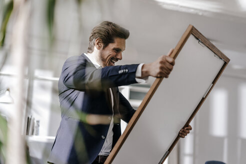 Excited businessman holding picture frame - KNSF01325