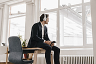 Businessman with tablet and headphones sitting on table - KNSF01331
