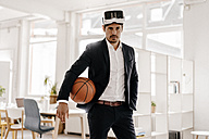 Businessman wearing VR glasses holding basketball in office - KNSF01337
