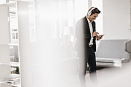 Smiling businessman with cell phone and headphones - KNSF01340