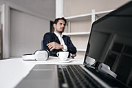 Laptop, headphones, coffee cup and businessman in background - KNSF01346
