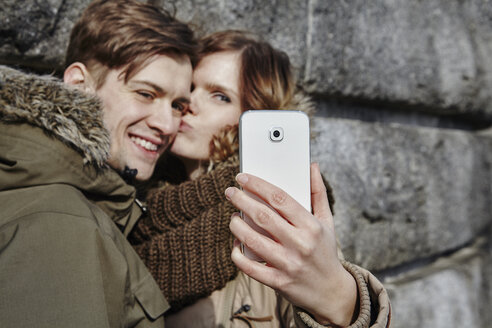 Happy young couple kissing outdoors taking a selfie - ANHF00034