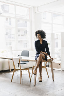 Young businesswoman sitting on her desk - KNSF01353