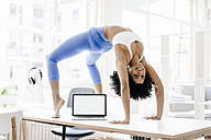 Young woman practising yoga with laptop by her side - KNSF01380