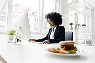 Young businesswoman working with hamburger on her desk - KNSF01386