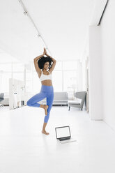Young woman practising yoga with laptop by her side - KNSF01407
