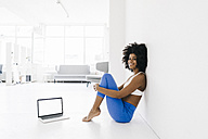 Fit young woman sitting on floor with laptop by her side - KNSF01410