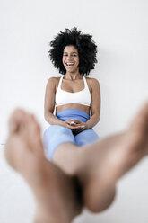 Barefoot woman sitting on ground, laughing - KNSF01428