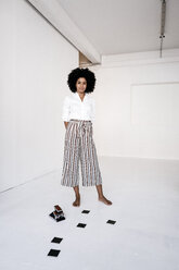 Young woman standing with instant camera and film on the floor - KNSF01437