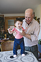 Happy Baby girl standing with help of Great-grandfather at home - GEMF01627