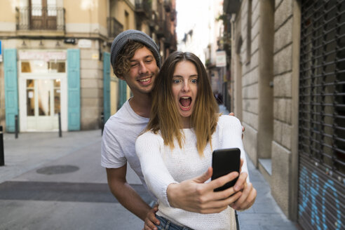 Happy young couple taking a selfie the city - KKAF00840