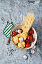 Uncooked Taglatelle, Spaghetti, tomatoes ans garlic bulbs in colander - MYF01918