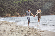 Happy couple running at the beach - ZOCF00388