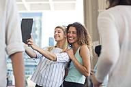Two happy women taking a selfie with tablet on urban square - ZEF13714