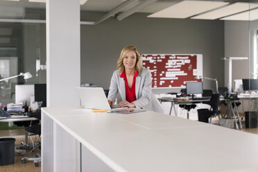 Portrait of smiling businesswoman using laptop in office - PESF00585