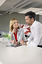 Businessman and businesswoman using futuristic portable device - PESF00594