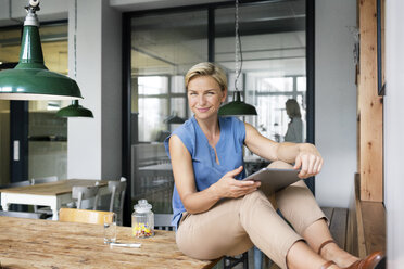 Portrait of smiling blond woman with tablet sitting on table - PESF00600