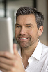 Smiling businessman using tablet - PESF00606