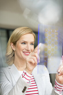 Smiling businesswoman using futuristic portable device - PESF00615