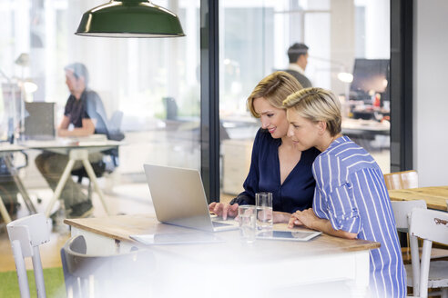 Two businesswomen sharing laptop - PESF00618