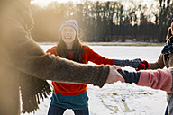 Friends ice skating in a circle on frozen lake - MFF03536