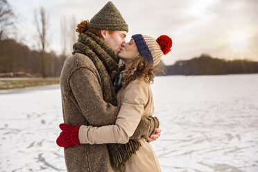 Couple kissing on frozen lake - MFF03539