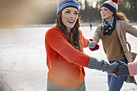 Female friends ice skating in a circle on frozen lake - MFF03542
