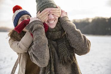 Playful couple on frozen lake - MFF03545