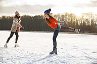 Two women ice skating on frozen lake - MFF03548