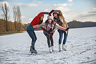 Three female friends ice skating and shaping a heart with their arms - MFF03551