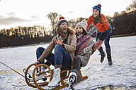 Friends having fun with sledge on frozen lake - MFF03554