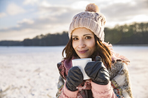 Portrait of smiling woman drinking hot beverage from a cup outdoors in winter - MFF03560