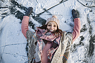 Portrait of happy woman lying down on frozen lake surface - MFF03563