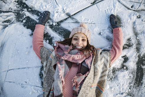 Portrait of happy woman lying down on frozen lake surface - MFF03563