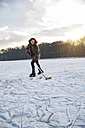 Man playing ice hockey on frozen lake - MFF03566