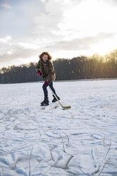 Man playing ice hockey on frozen lake - MFF03566