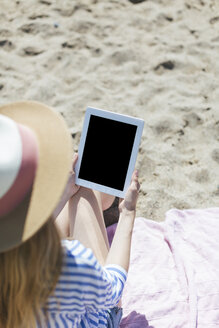 Woman sitting on the beach with tablet - JPF00209