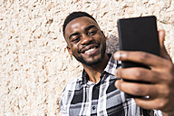 Portrait of smiling young man taking selfie with cell phone - ABZF02028