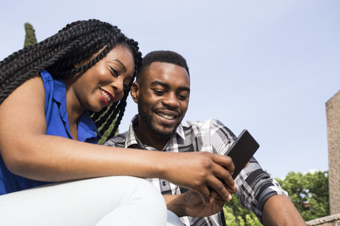 Portrait of smiling young couple looking at cell phone - ABZF02031