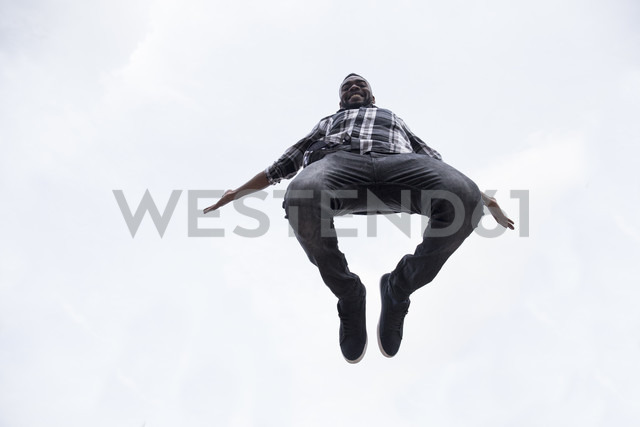 Happy young man jumping in the air - ABZF02034