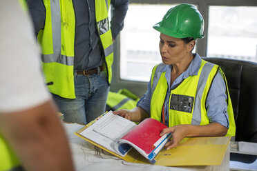 Female quarry worker checking files in office - ZEF13747