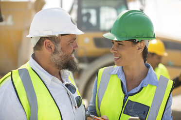 Male and female quarry workers discussing on site - ZEF13759