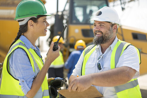 Male and female quarry workers discussing on site - ZEF13762