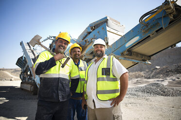 Colleague workers at quarry standing in front of digger - ZEF13777