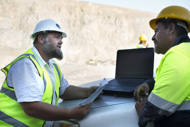 Workers at quarry discussing, leaning on car bonnet - ZEF13783