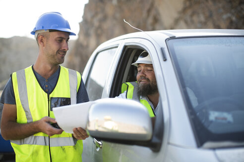 Worker handing over documents to colleague sitting in car - ZEF13786
