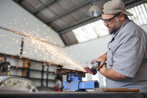 Mechanic using angle grinder in car workshop - ZEF13795